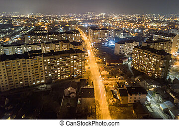 High rise apartment buildings with illuminated windows in city residential area at night.