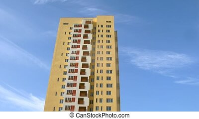 High-rise building of yellow color stands against blue sky,...