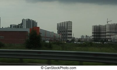 high rise buildings of a big city view from the window of the car while driving slow motion video full hd
