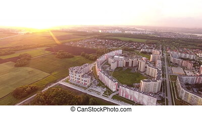 high-rise houses and fields at sunset