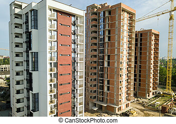 High-rise residential apartment buildings and tower crane under development on construction site. Real estate development.