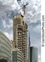 high rise under construction with crane and cloudy sky