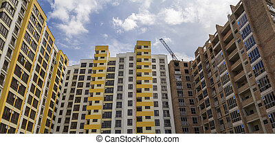 High rising multistory residential apartment brick building and working crane on block under construction on blue sky background. Modern urbane architecture, investments, buying and selling concept.