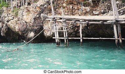 High rocks in the sea with old small wooden pier. slow...