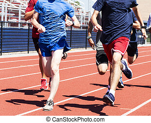 High school boys traiining together on a red track