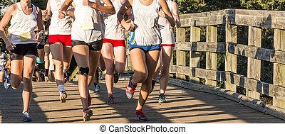 High school cross country girls race over a bridge