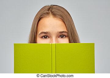 teenage student girl hiding over book