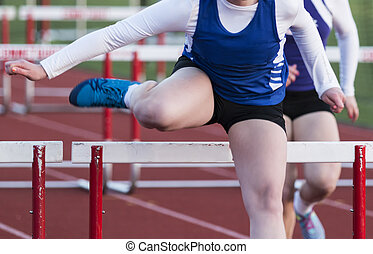 High school girl racing the hurdles