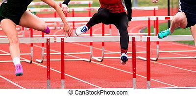 High School girls racing in the hurdles