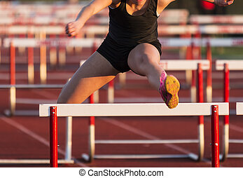High school girls racing the 100 hurdles