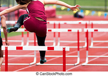 High School Girls Track hurdle race from behind