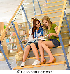 High school library students sitting on stairs