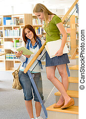 High school library students with books - Two female...