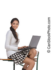 High school or college female schoolgirl student sitting on desk typing on laptop