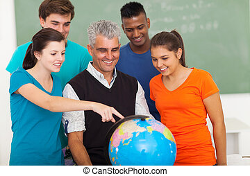 high school students and teacher looking at globe