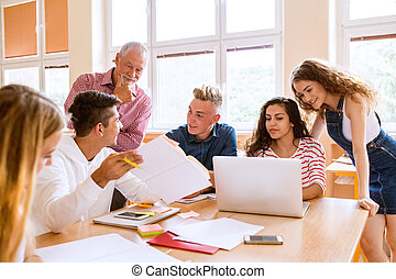 High school students and teacher with laptop.