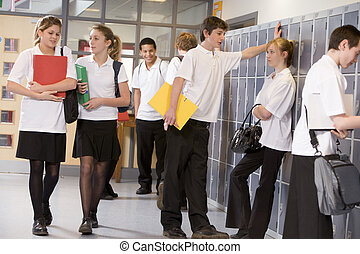 High school students by lockers in the school corridor