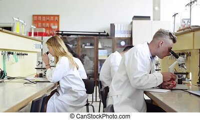 High school students with microscopes in laboratory.