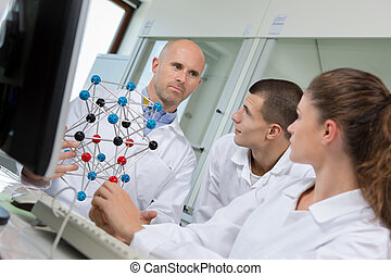 high school students with teacher in chemistry class