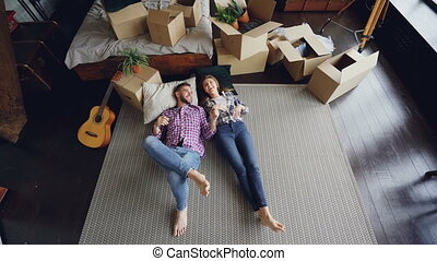 High shot of young couple lying on floor of their new house...