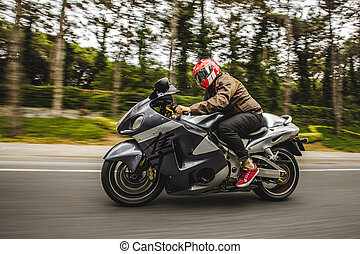 High speed motorcycle biking on the road accross the forest