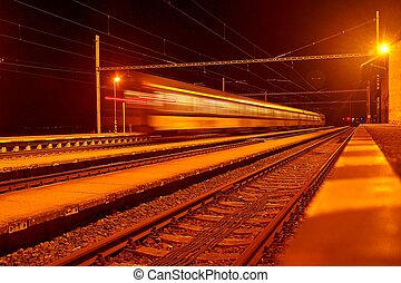 High speed passenger train on tracks with motion blur effect at night. Railway station in the Czech Republic