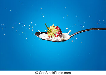 High-speed photo of strawberries falling into milk -...