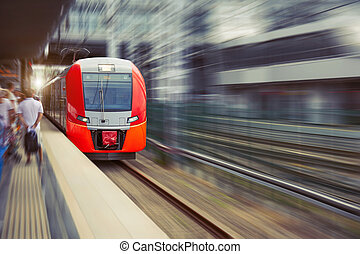 High speed suburban train with motion blur rides city station.