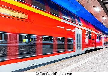 High speed train at railway station platform at night