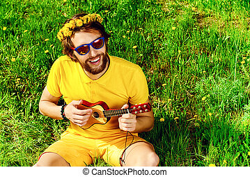high spirits - Happy carefree young man sitting on a grass...