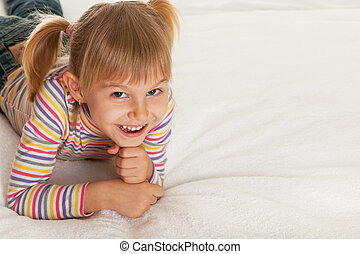 High spirits - A smiling little girl is lying on the...