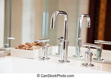 High spout faucet and bowl  in front of a mirror