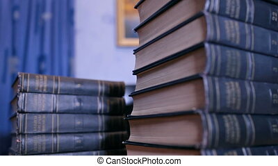 High stack of books on the desk in library