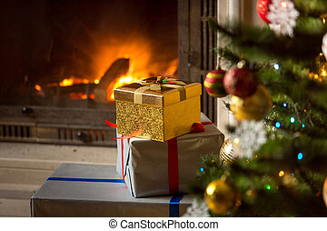 High stack of Christmas presents with burning fireplace