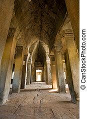 High stone corridor in Cambodian temple ruins