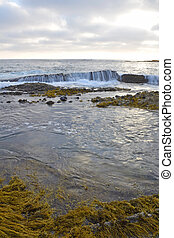 Waves crash over the rocks in Laguna Beach, California during high tide.