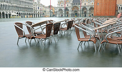 High tide in Venice Island and the chairs and tables of ...