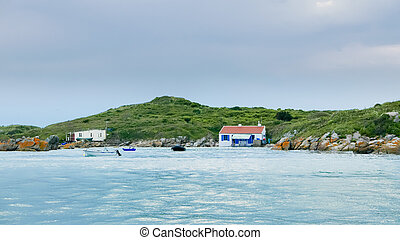 High tide around a green island int he archipelago of Iles de Chausey. Small houses at the waterfront just above the surface. Small boats in front. Brittany, France.