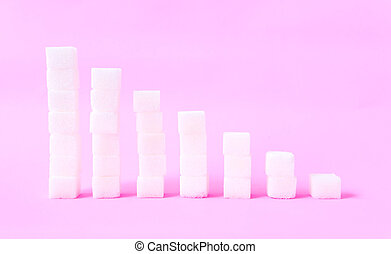 High to low stacks of sugar cubes with pink background, health care diet concept