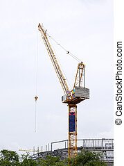 High tower crane in the construction site.