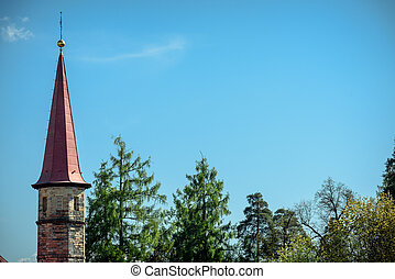 High tower of an ancient castle from behind trees against the blue sky