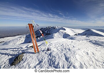 Pair of back country ski, the cross of the top and buddhist flags in the wind, in scenic winter wide angle landscape.