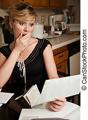 High utility bill - Blond woman in casual attire with hand...
