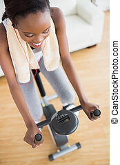 High view of a black woman sitting on an exercise bike