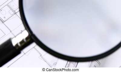 High view of magnifying glass over architecture plans