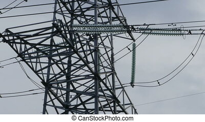 High-voltage insulators on a steel power line support camera...