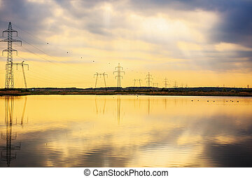 High-voltage poles reflected in the water of a lake