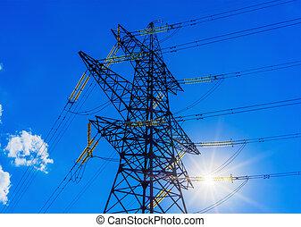 high voltage post. High-voltage tower sky background sun.