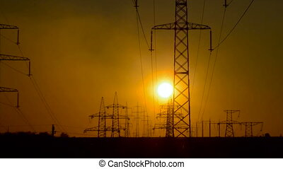 High-voltage power lines at sunrise