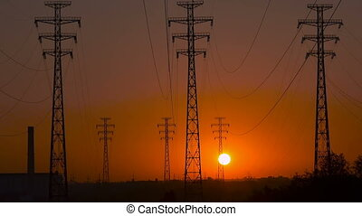 High-voltage power lines at sunrise.